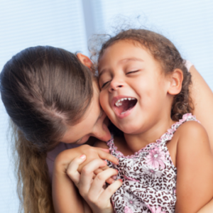 Mother and daughter laughing together outside