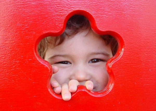 Little boy looking through a star cut out in a piece of playground equipment