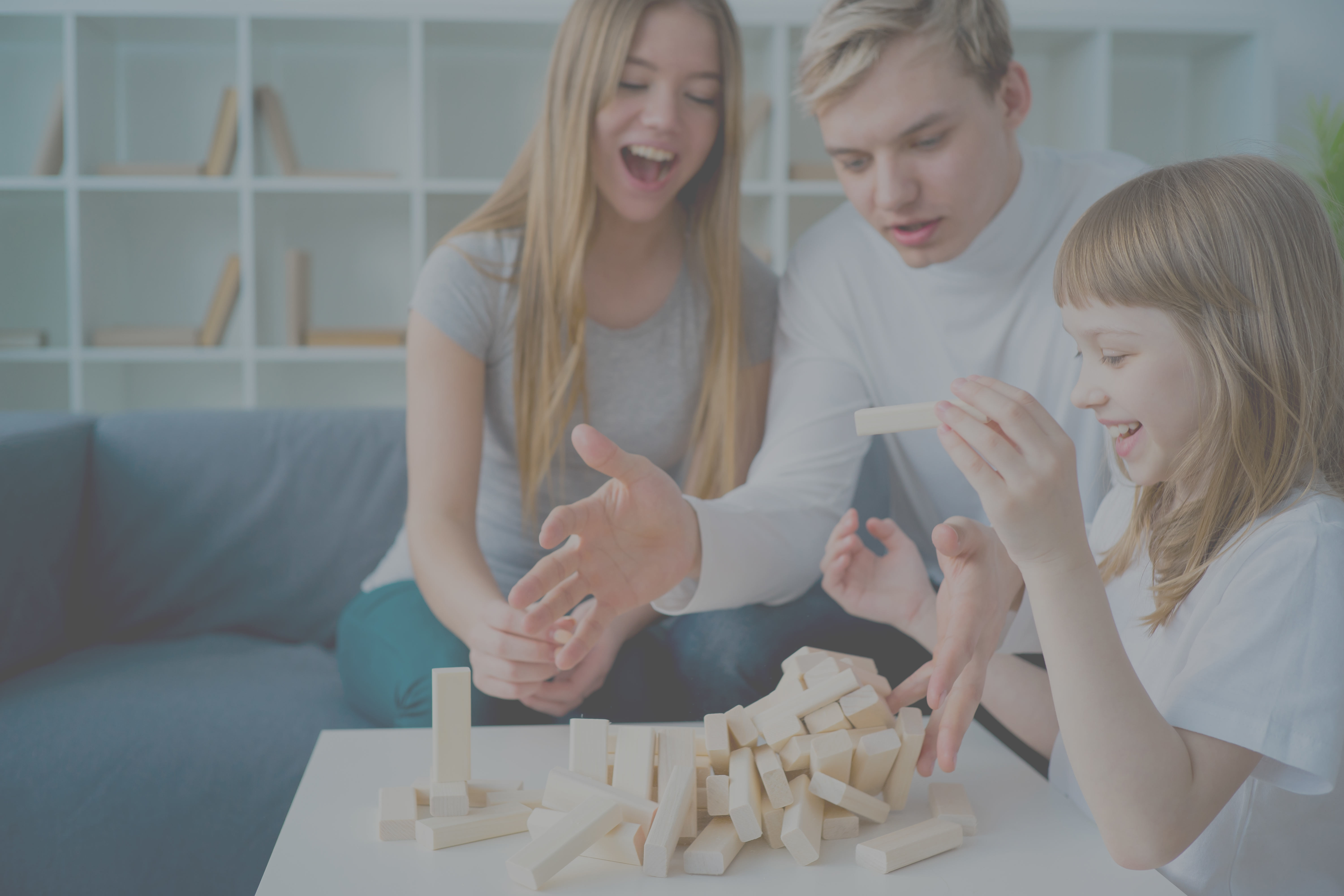 Brother and two sisters play Jenga in the living room as the tower of blocks falls