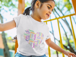 Girl wearing white heart t-shirt from Child Family and Guidance Center on a playground