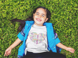 Girl wearing the white heart t-shirt while laying on the grass