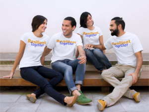 Co-ed group wearing white Resilient Together t-shirts with color print