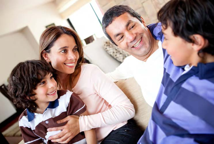 Mother, father and two sons relax in a living room